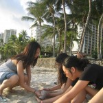 Lil' T, Emily, and Connie building a sandcastle